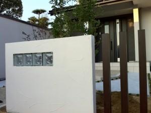 白い塗り壁とスリットフェンス